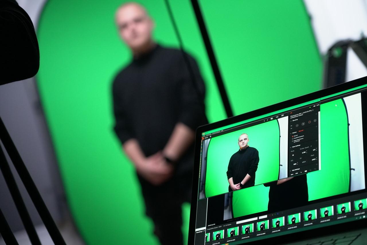 Mitarbeiter wird vor einem Greenscreen fotografiert