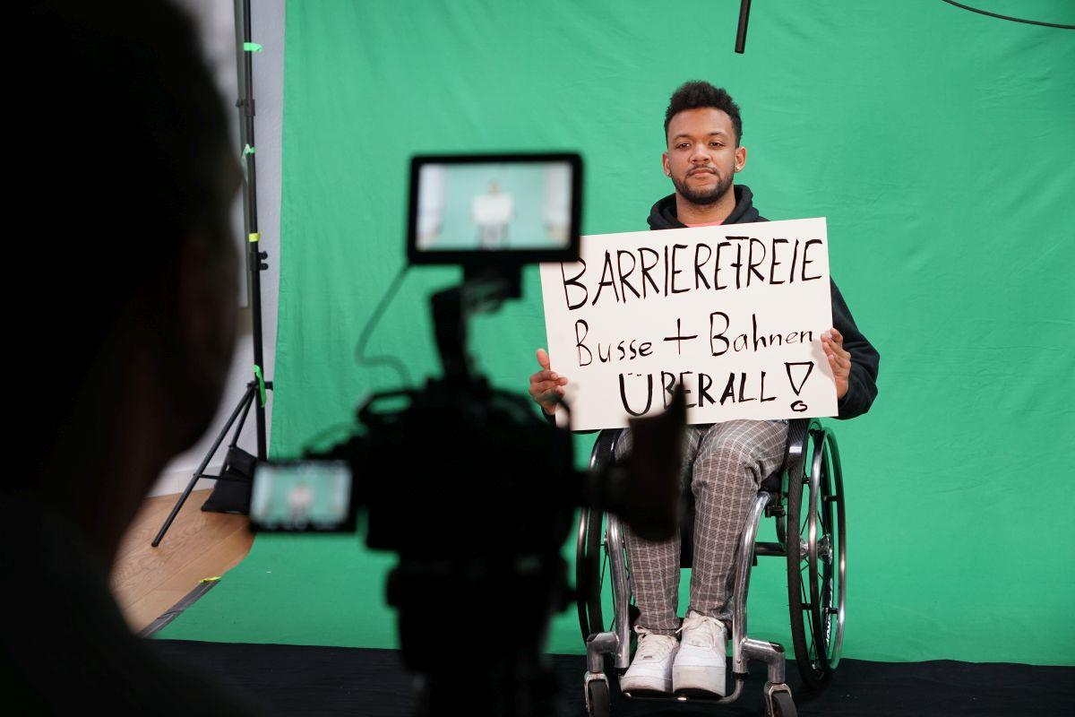 Leeroy Matata sitzt am Greenscreen-Set mit einer Forderung zum 5. Mai