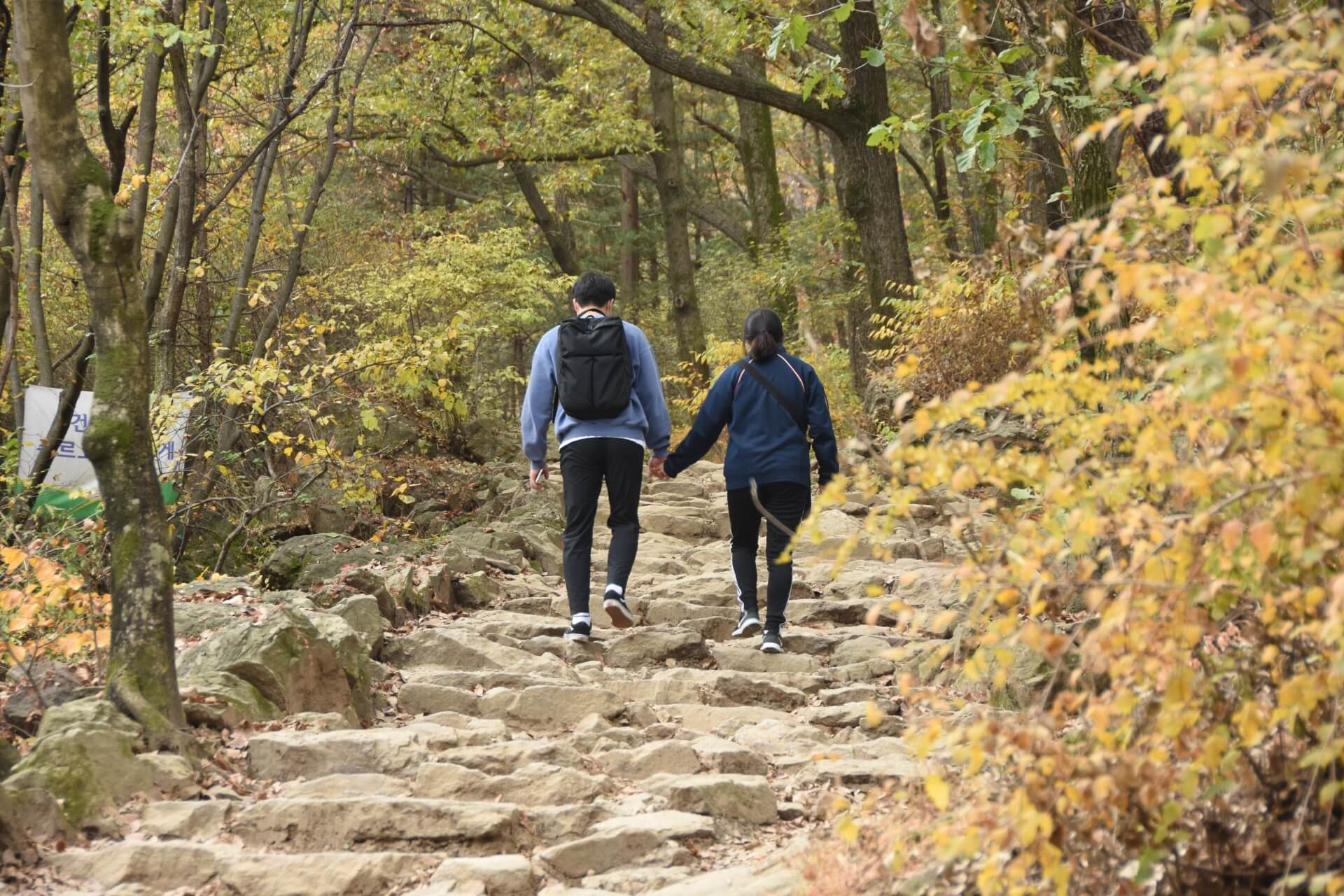 active couple walking on a rocky trail staring their journey