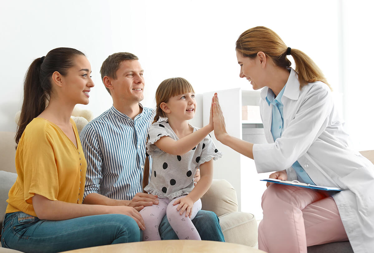 young girl sitting on her dad's lap touching hands with her ConciMed doctor during her primary care house call