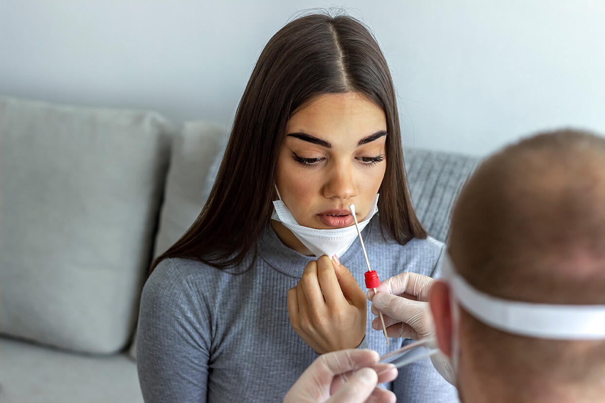 lab technician holding a nasal swab leaning to test a young woman with a mask for covid-19