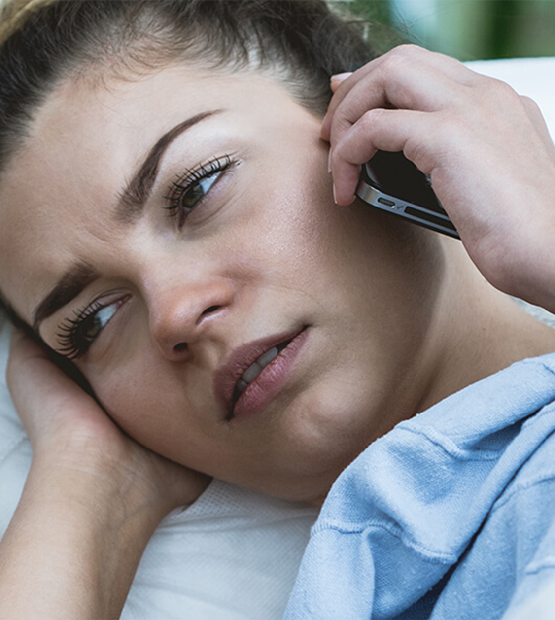 young woman sick in bed holding her phone to her ear calling ConciMed to book a Covid-19 test