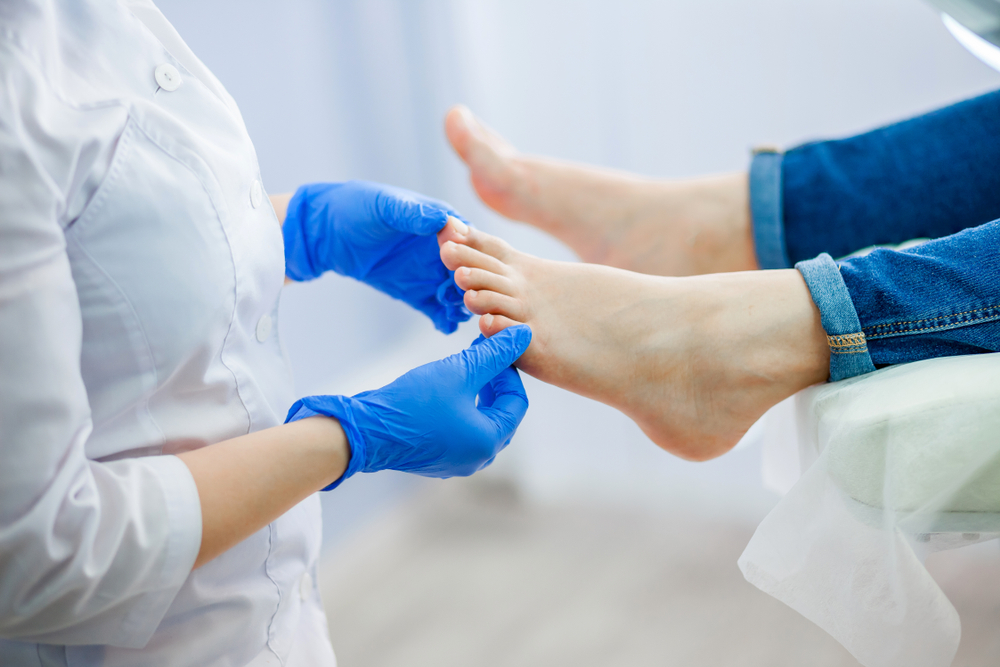 concimed podiatrist wearing gloves examining her patient's feet at home