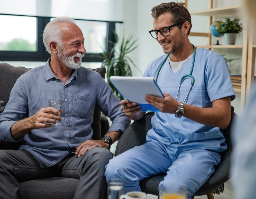 older man during his podiatry consultation laughing with his concimed doctor