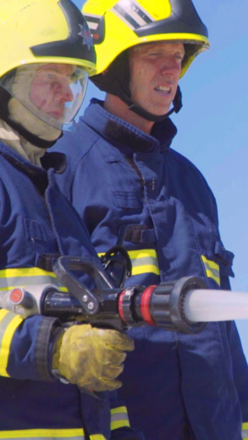 Two firefighters stood side by side fighting a fire.