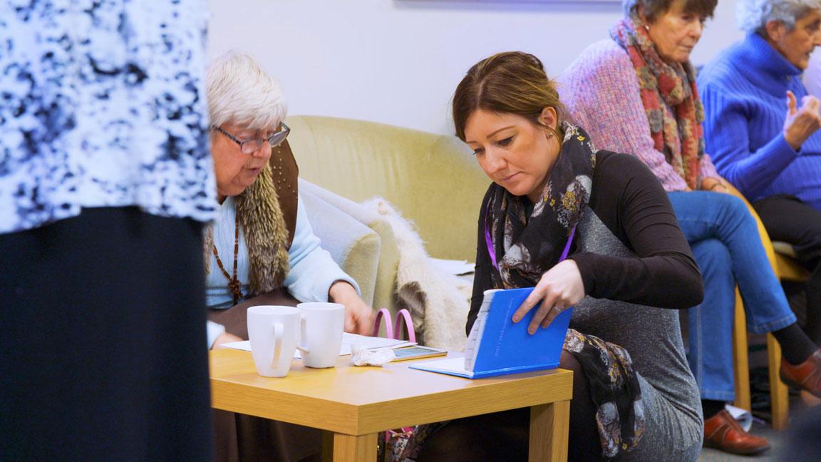 Volunteer helping an older patient.