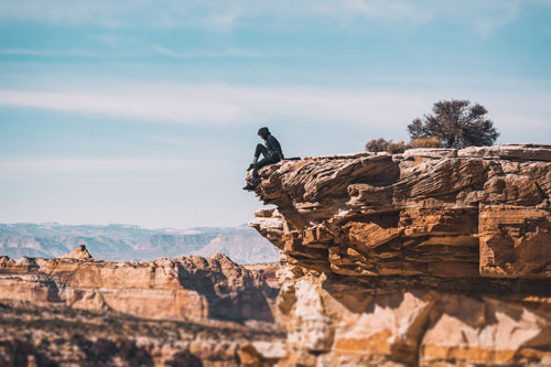 A man looking over the edge of a cliff