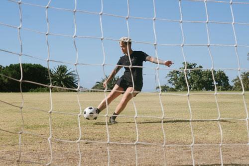 A woman kicking a ball into a net.