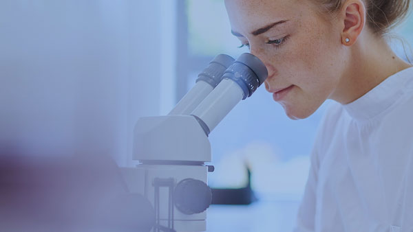 A female scientist looking through a microscope.