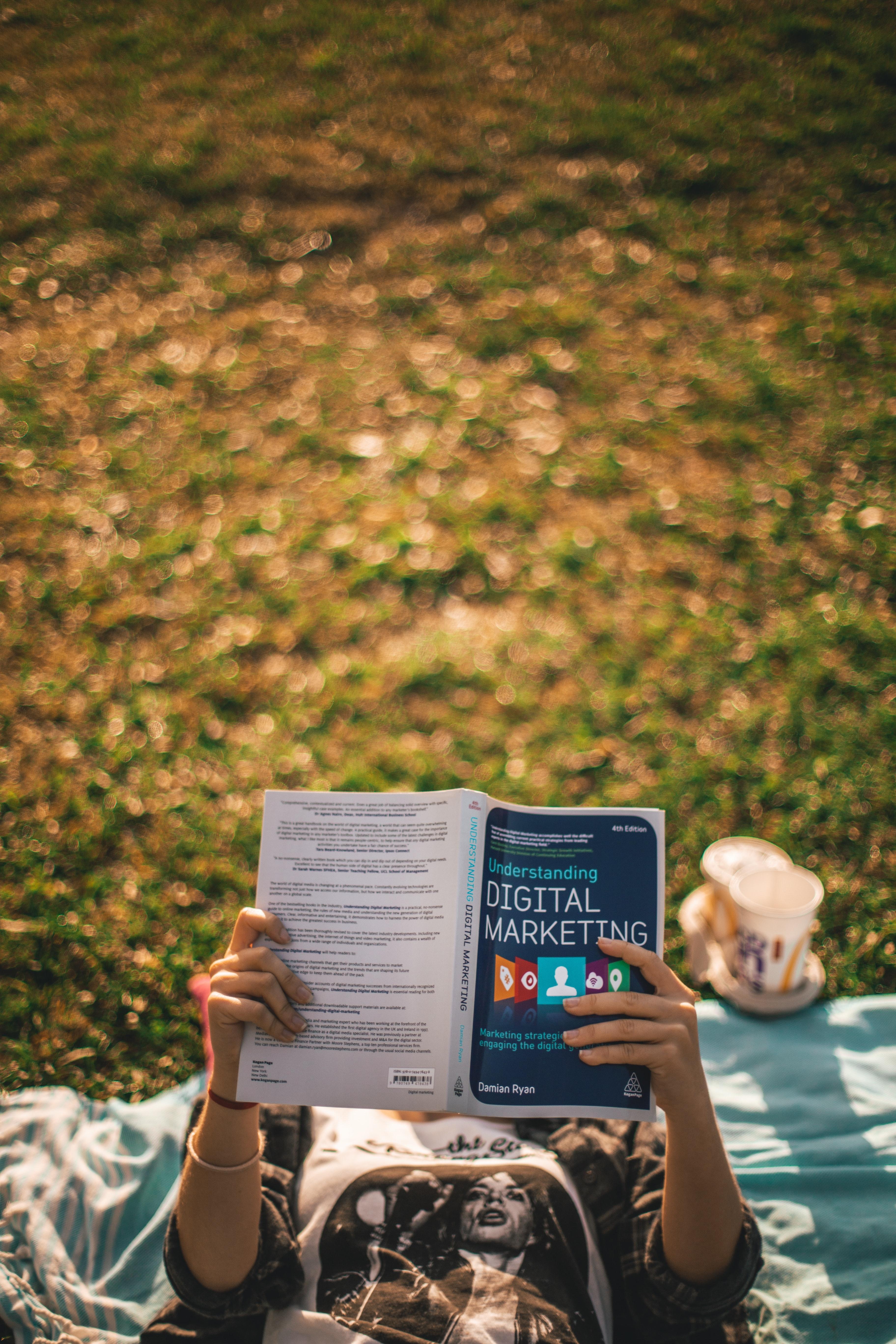 "person reading book entitled ""digital marketing"""