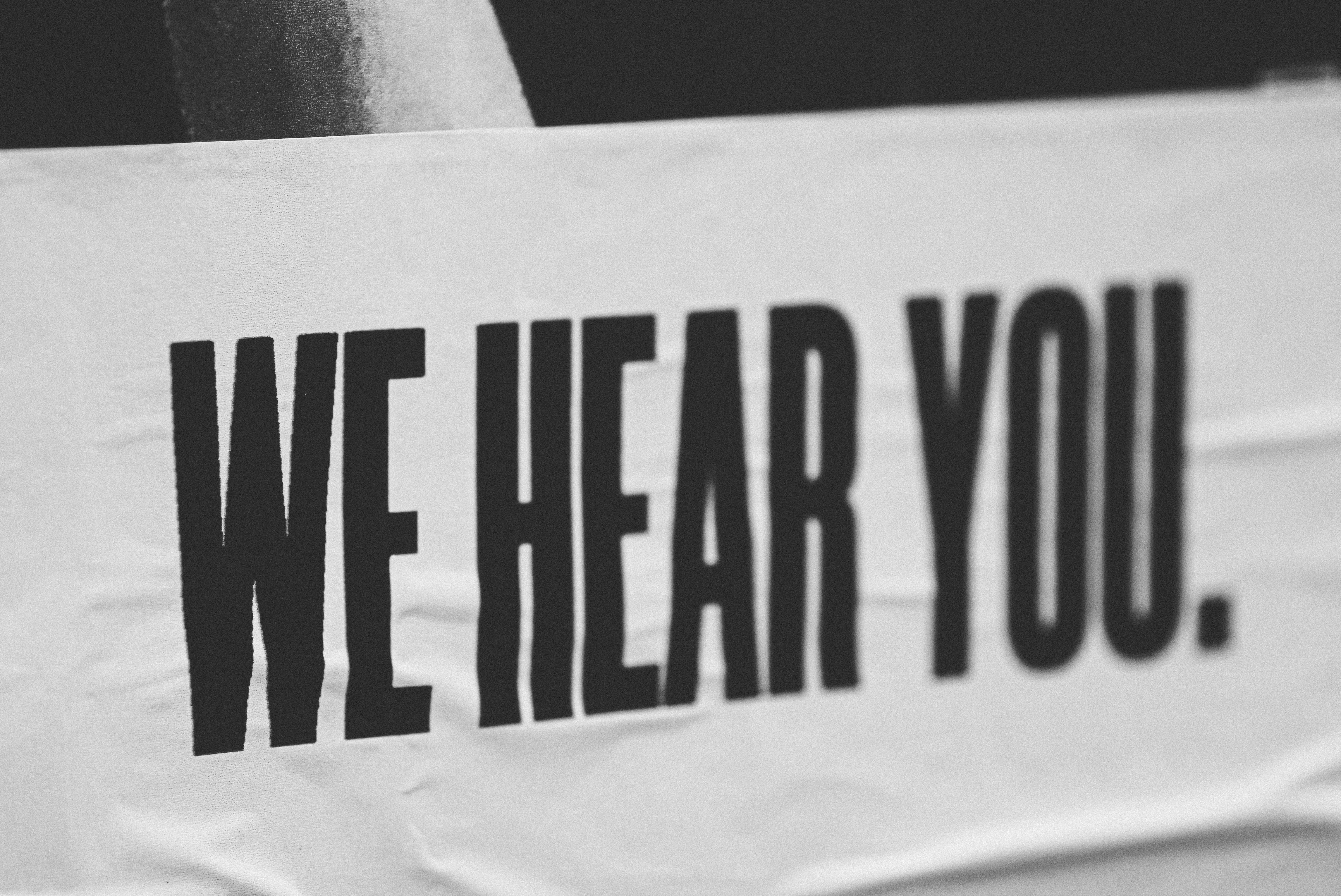 We Hear Your black and white banner
