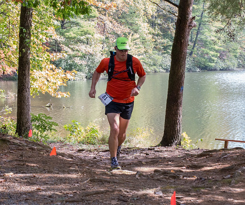Man running in woods overlooking a river.