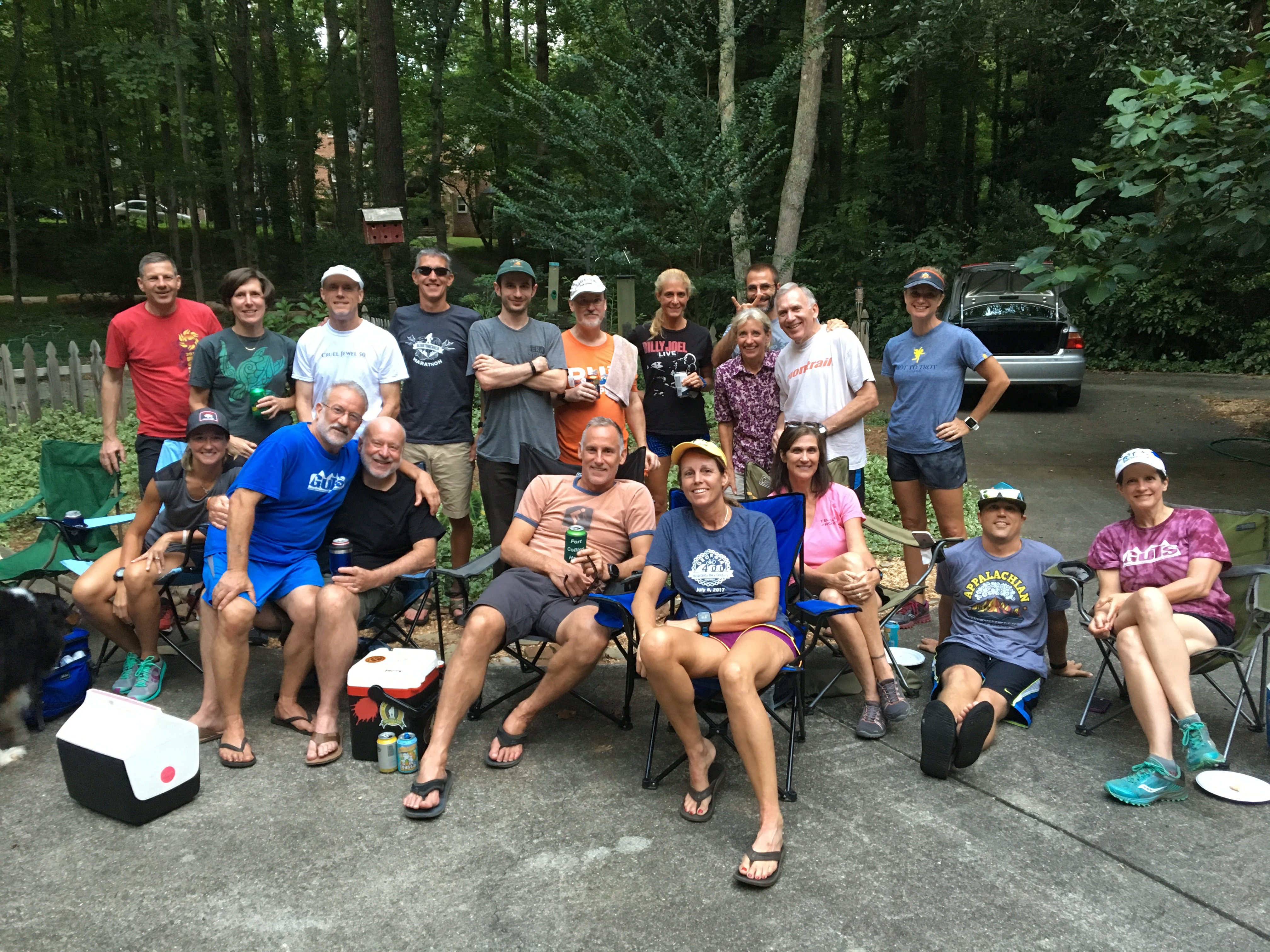 Group of runners posing for a picture after a group run outside the trail entrance sitting in chairs with coolers.