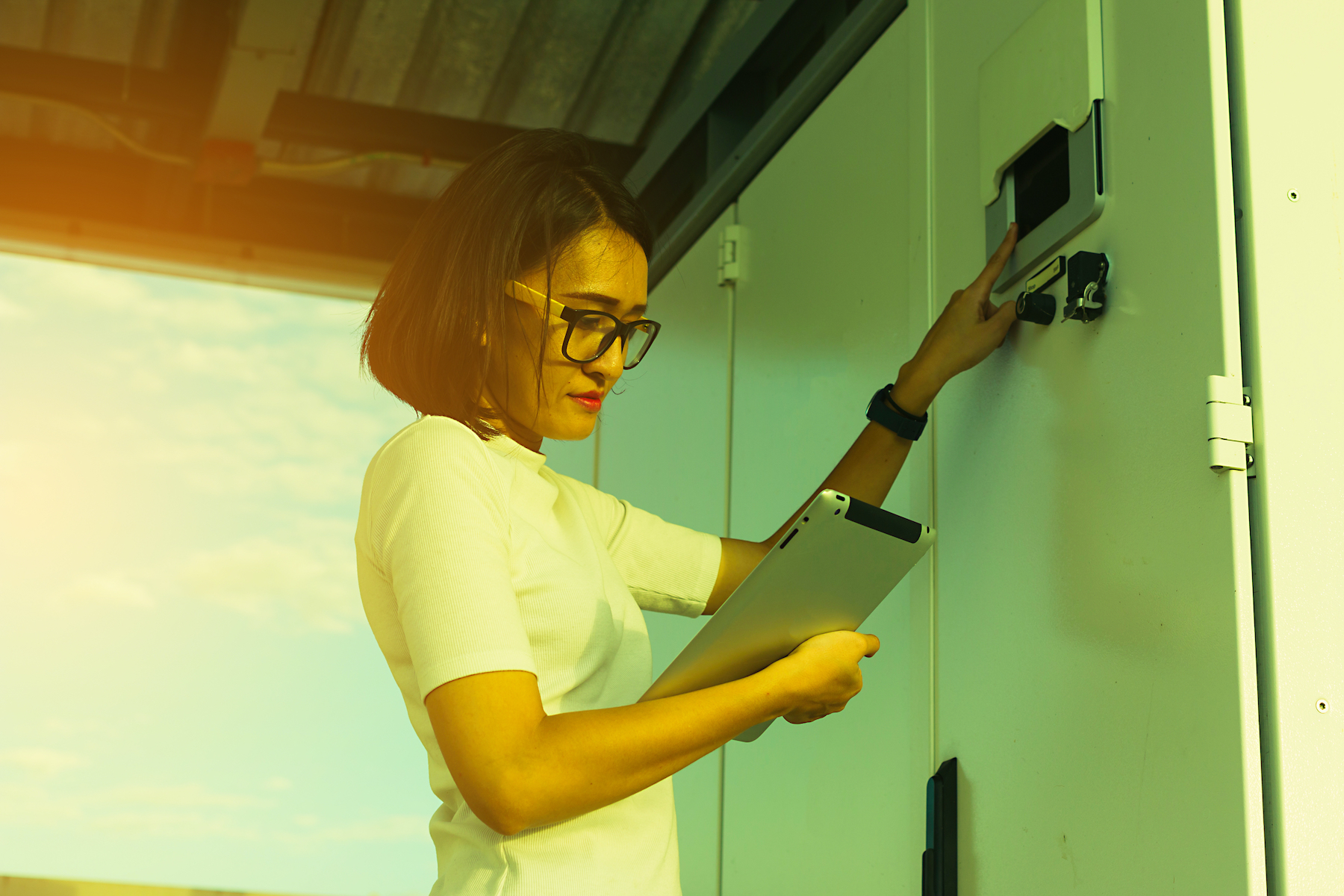 Woman uses tablet to configure battery storage system.