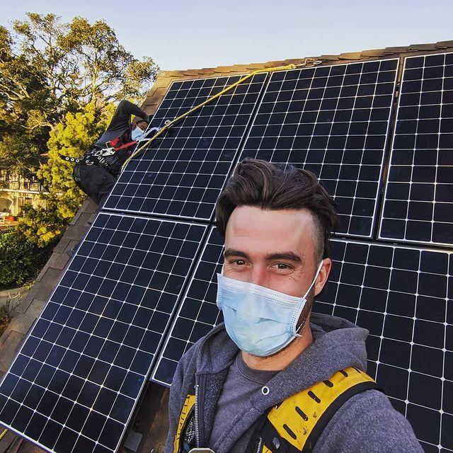 man wearing mask taking selfie with solar panel