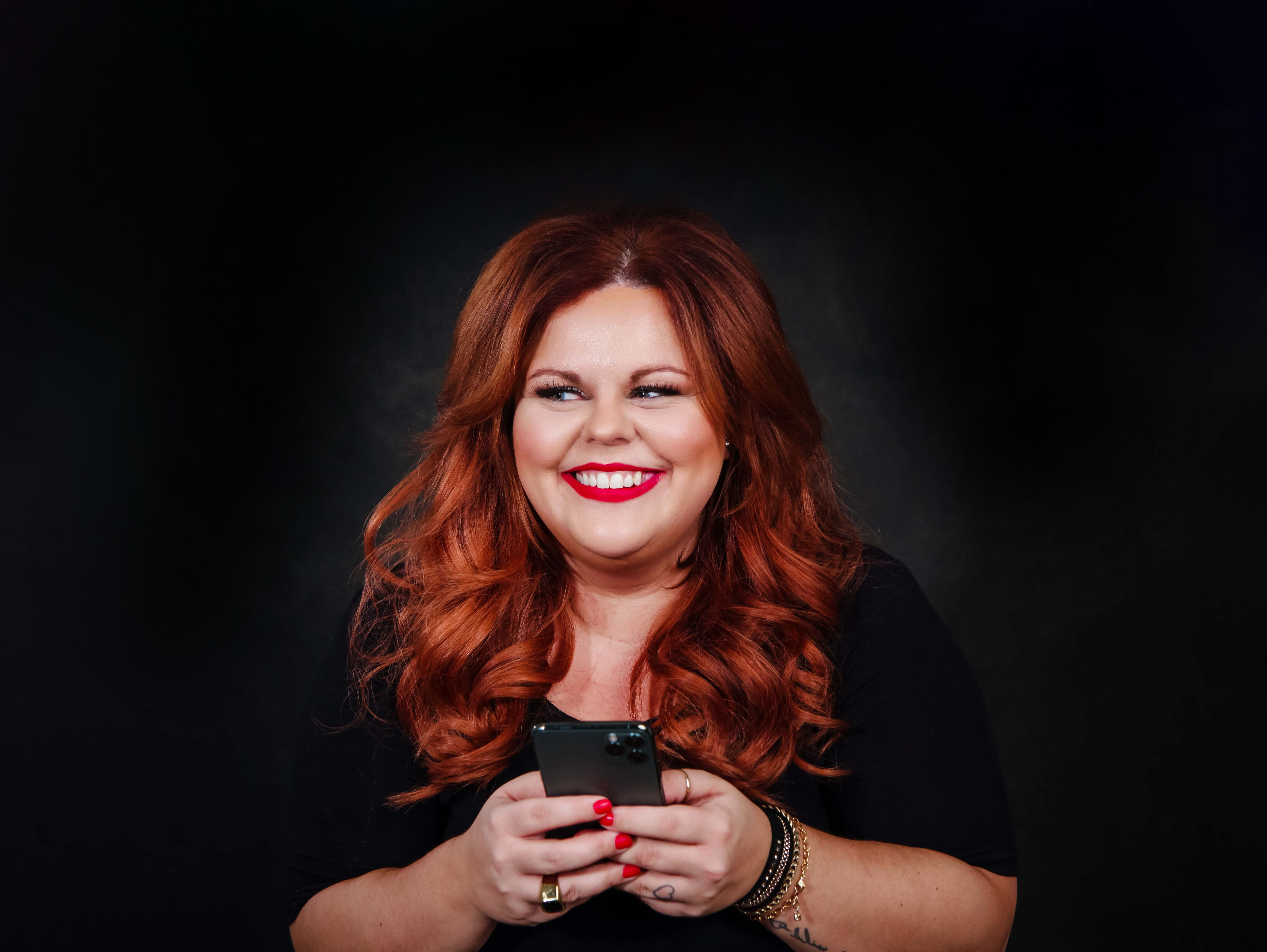 Karine Parthenais smiling and holding an iPhone