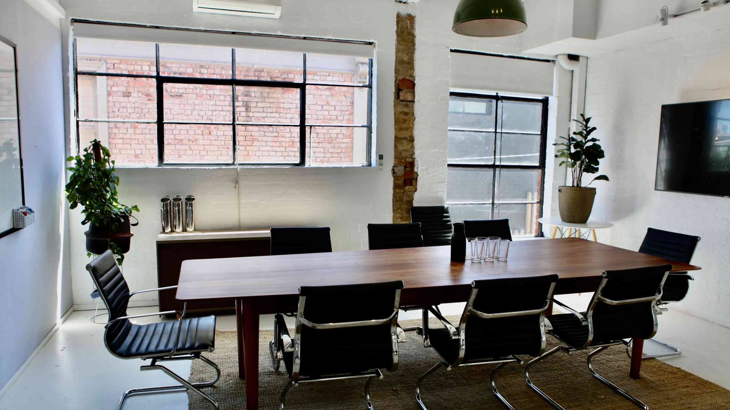The spacious private board room, filled with natural light. The room seats 10 people and has a TV with Apple TV and HDMI in the background.