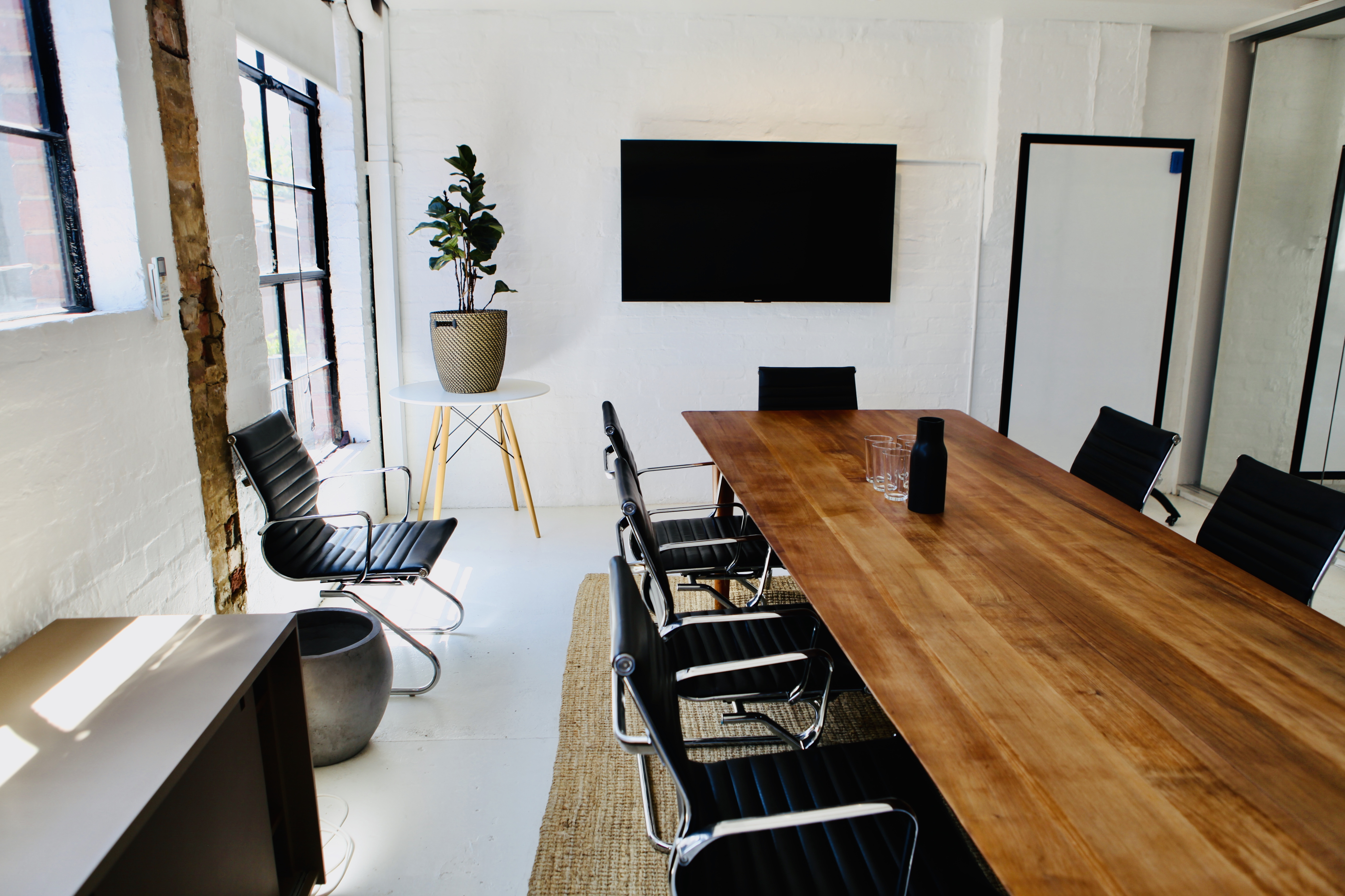 The board room for hire at Service Cowork, featuring an oak 12-person table, Apple TV and a large portable whiteboard