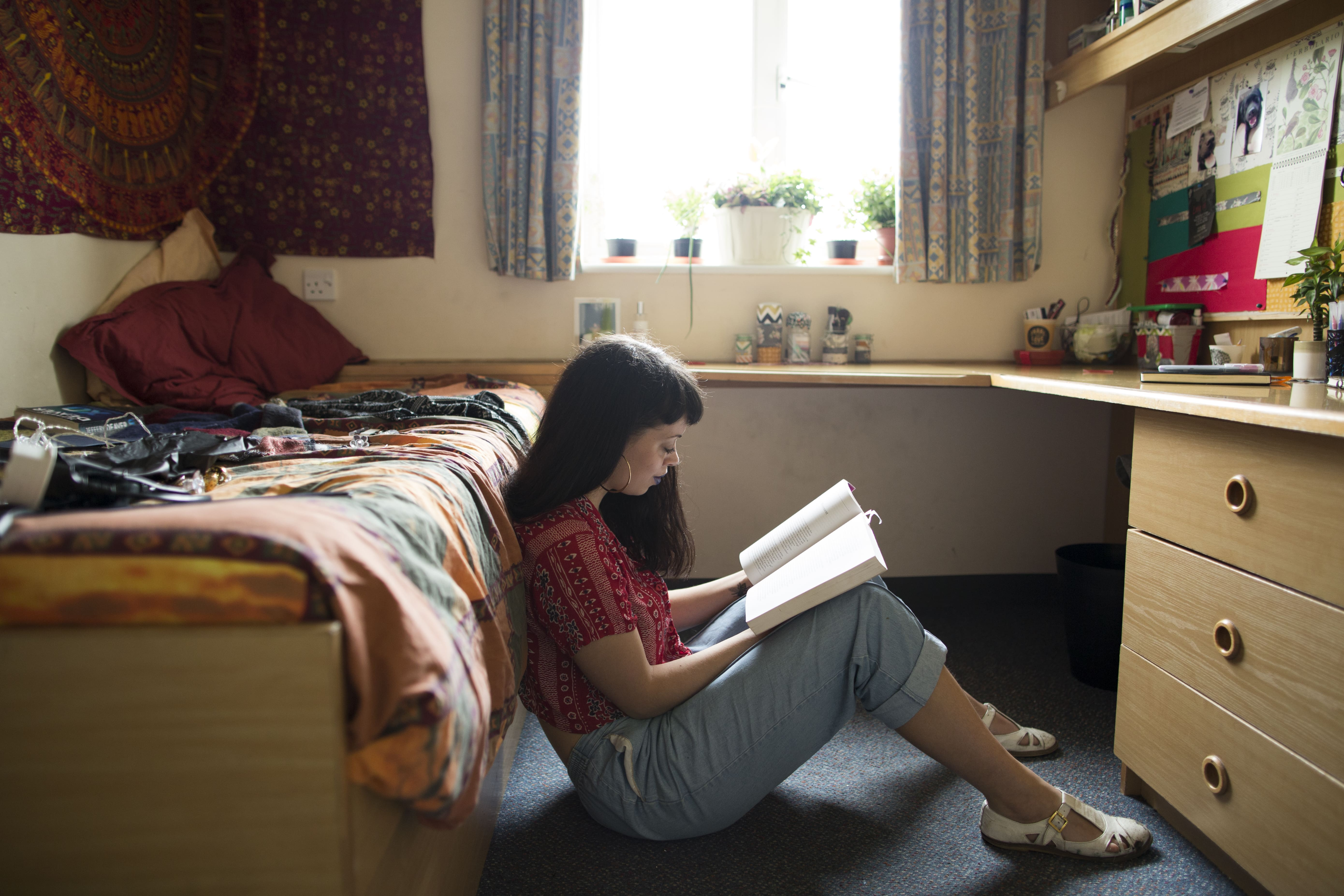 Student reads book in their room