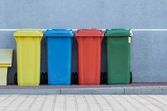 Line of different coloured recycling bins