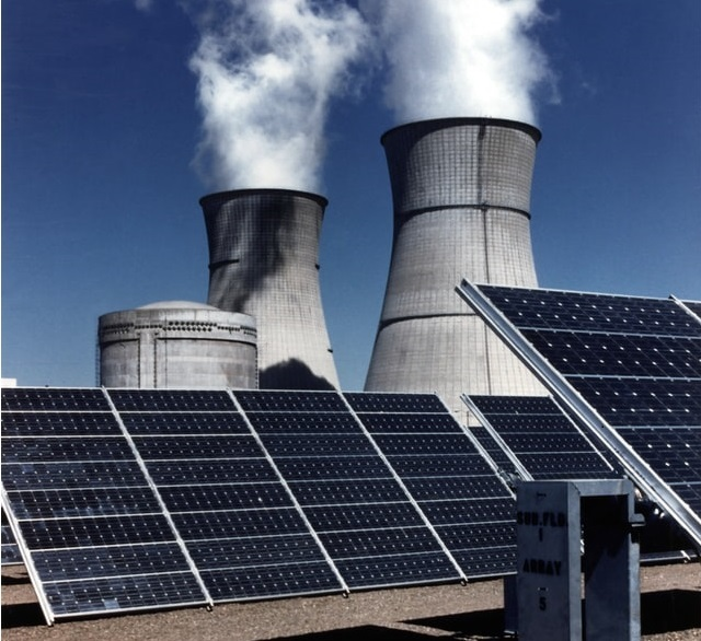 solar panels in front of a power station chimney