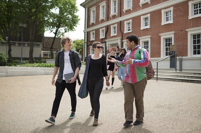 three students walking outside a building