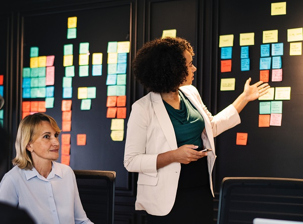 diverse office workers looking at post it notes