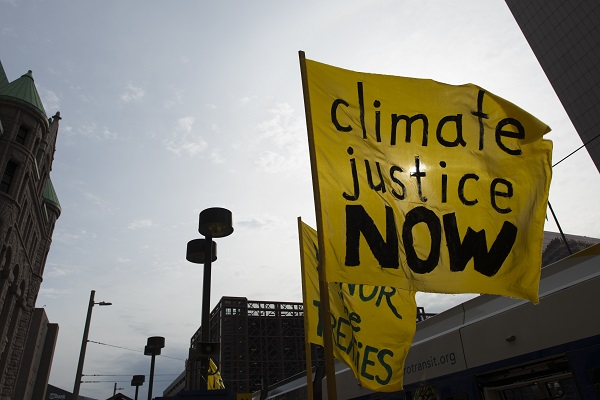 """A flag stating """"climate justice now"""" against the background of a sunny sky"""