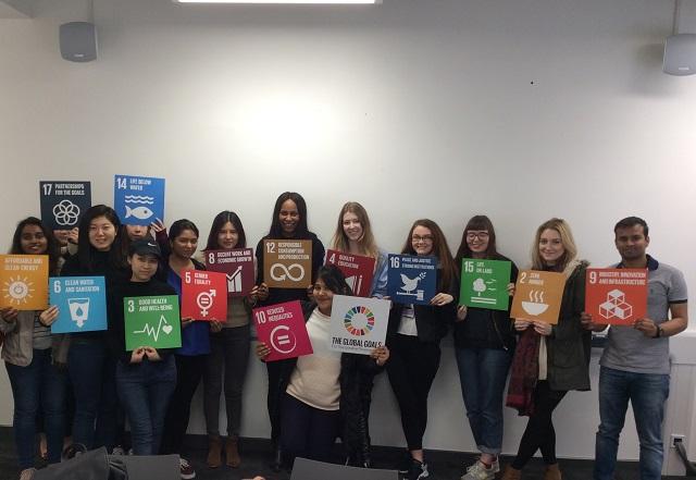 Students holding SDG (sustainable development goal) signs at De Montfort University.