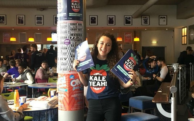 Student holding Kale Yeah posters in university canteen