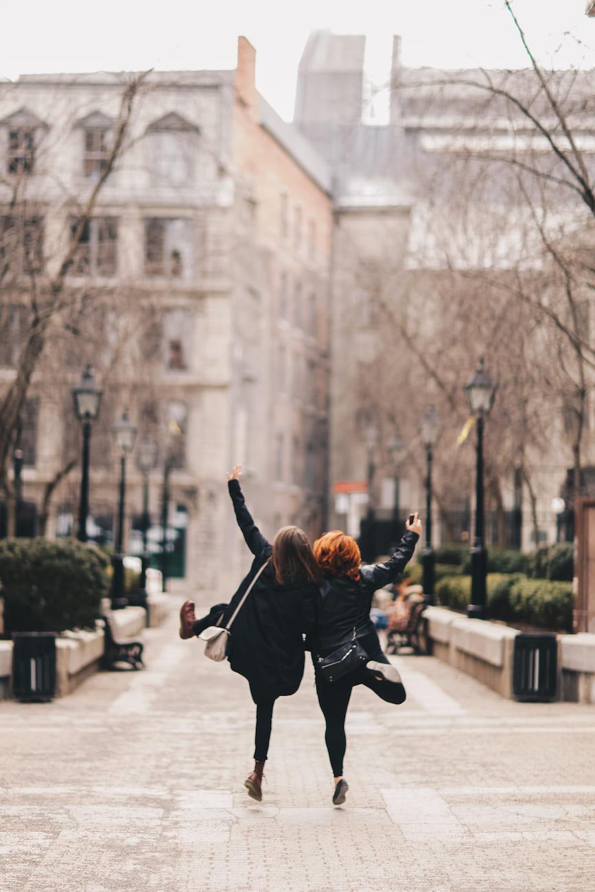 Two people joyfully walking down a city street