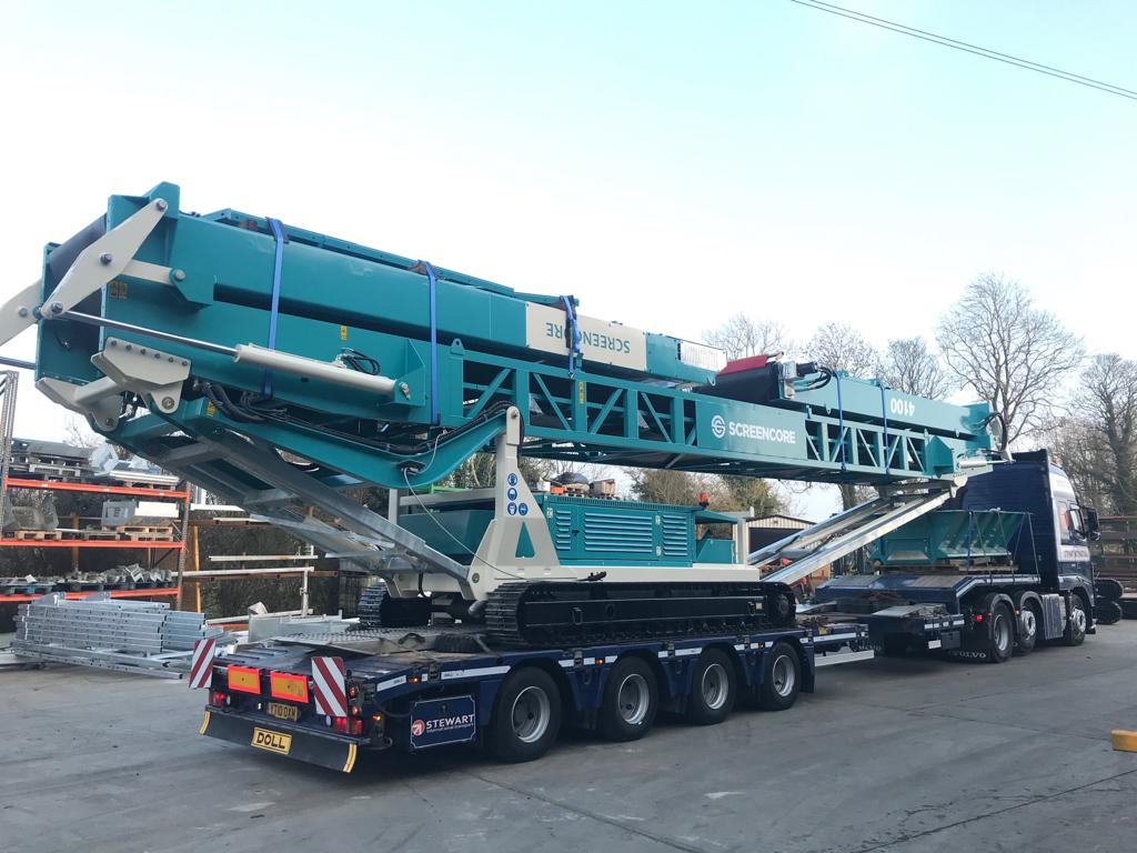 Screencore heavy machine on trailer being delivered to customer via machinery partner