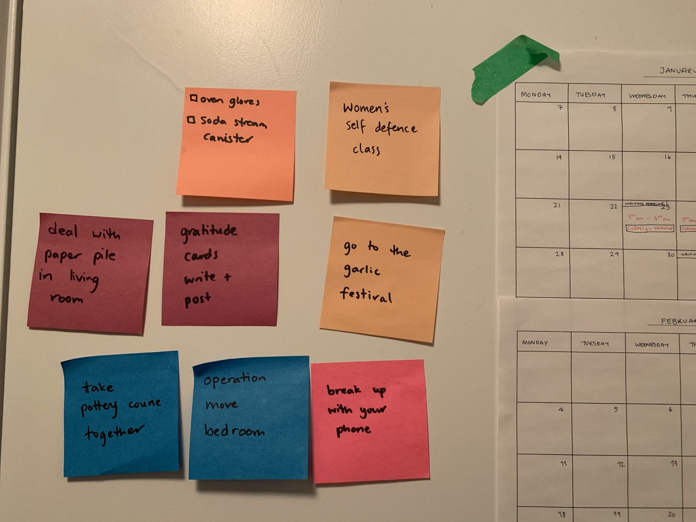 a cluster of post it notes with tasks on them beside a calendar on a wall