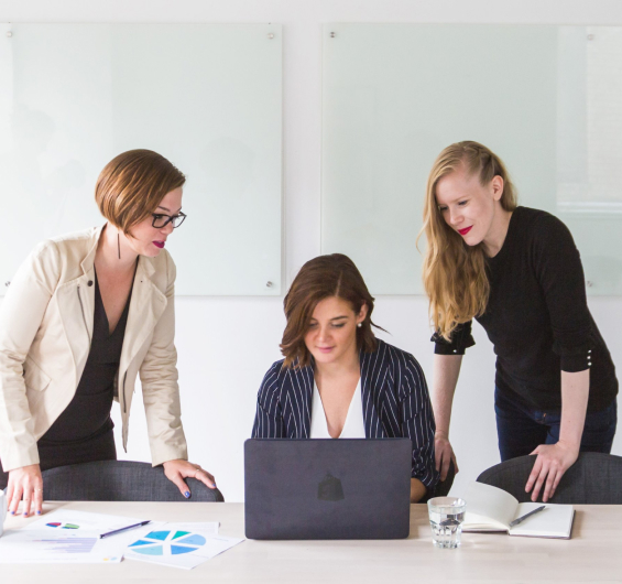 A lady using laptop and two others are standing behind her in the office