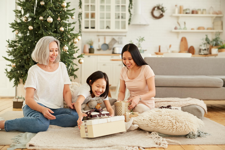 Familie bestehend aus drei Frauen öffnet Geschenk vor einem Weihnachtsbaum