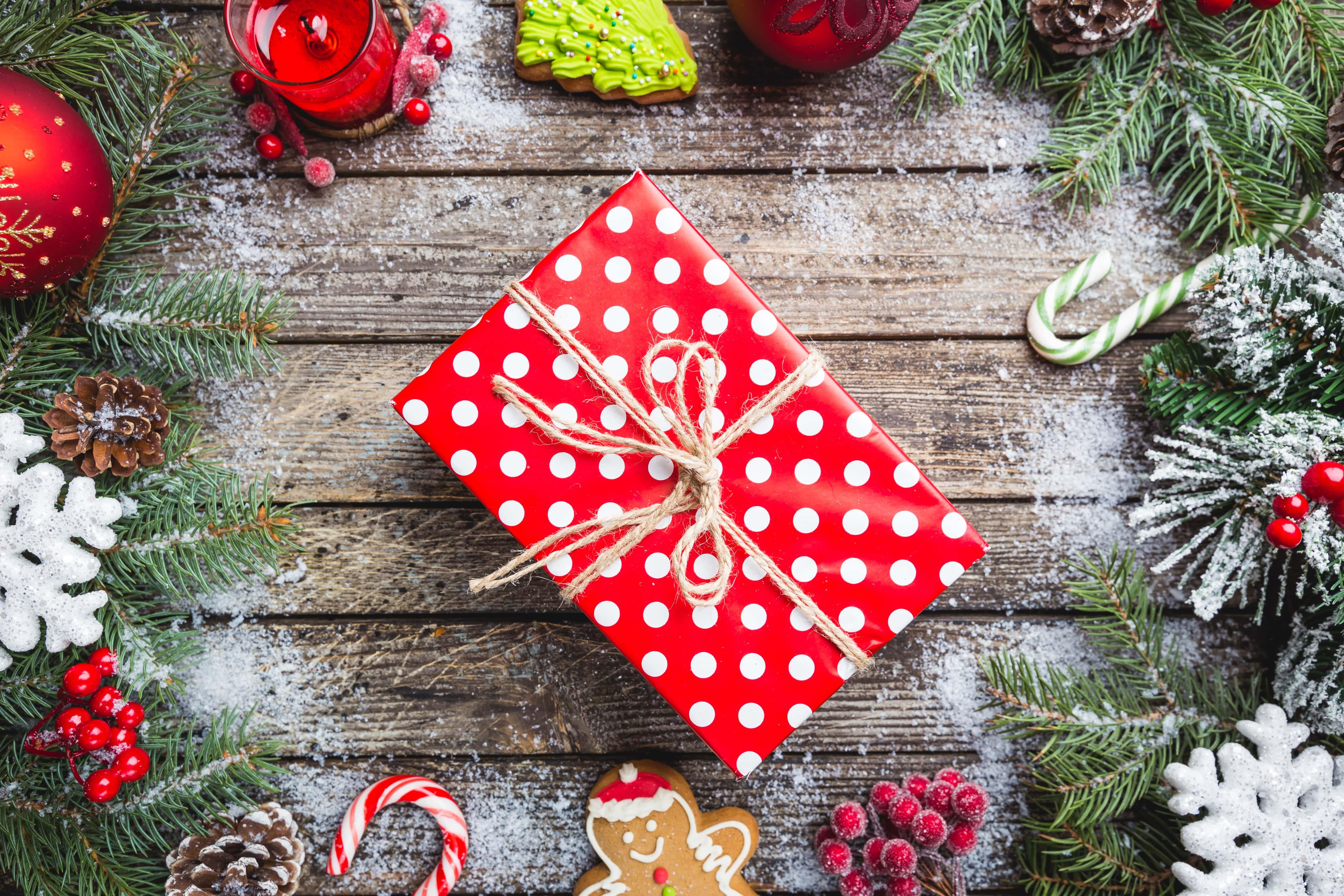 Geschenk mit rotem Geschenkpapier, weißen Puinkten einer Schleife und Tannenzeigen