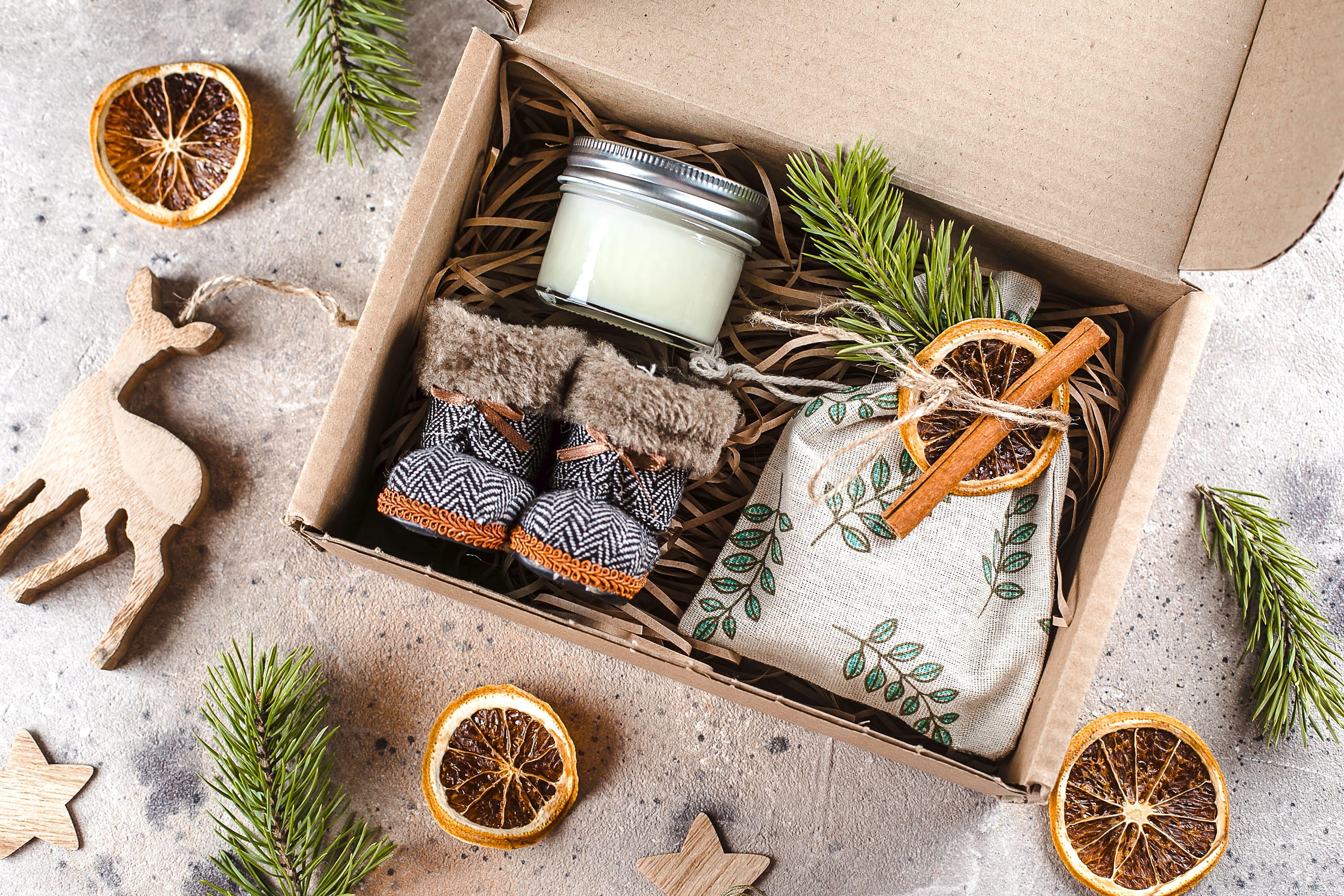Geschenkbox mit Schuhen und Kerze und Dekoration aus Tannenzweigen und Orangenschalen