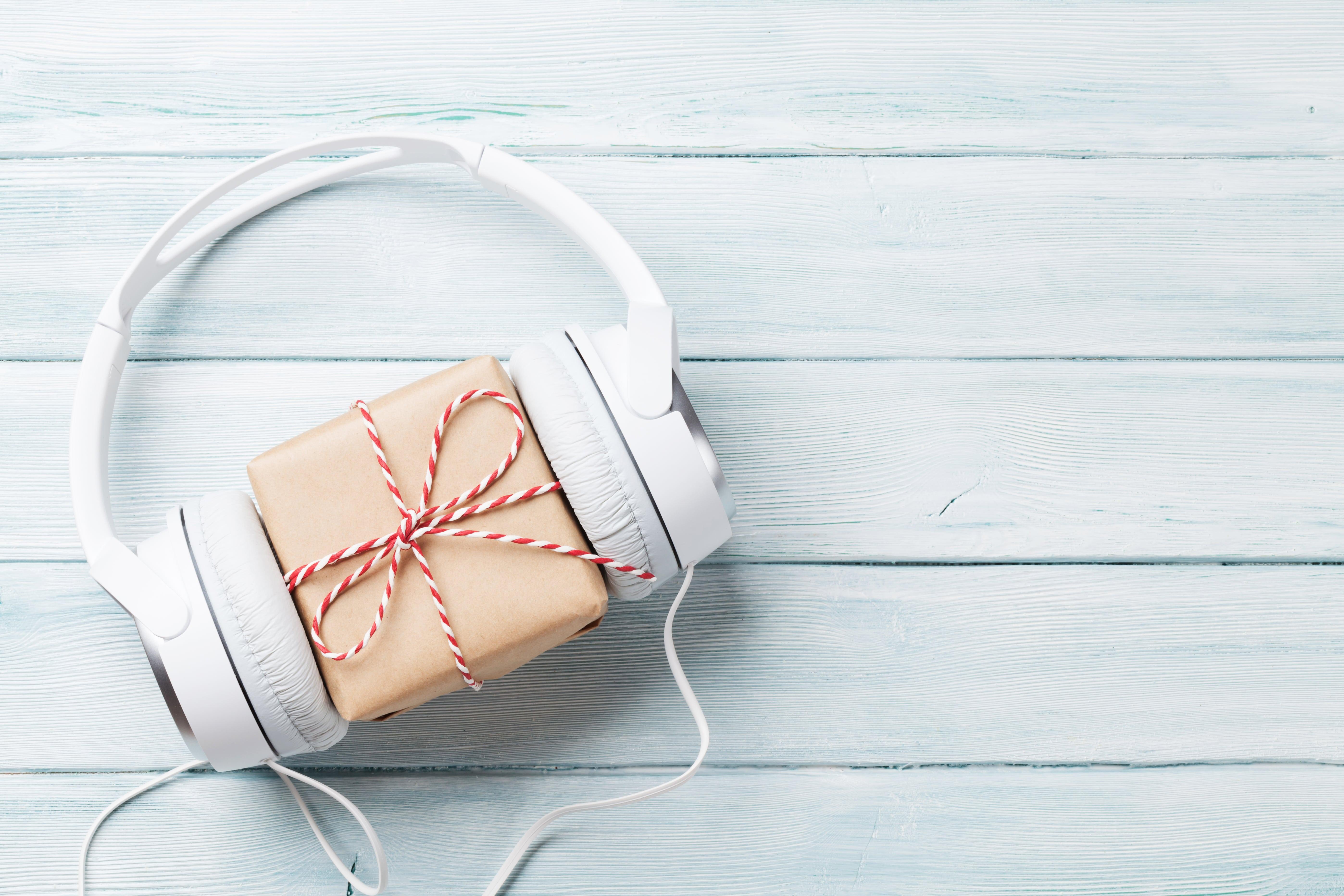 Weiße Kopfhörer um ein Geschenk mit einer Schleife