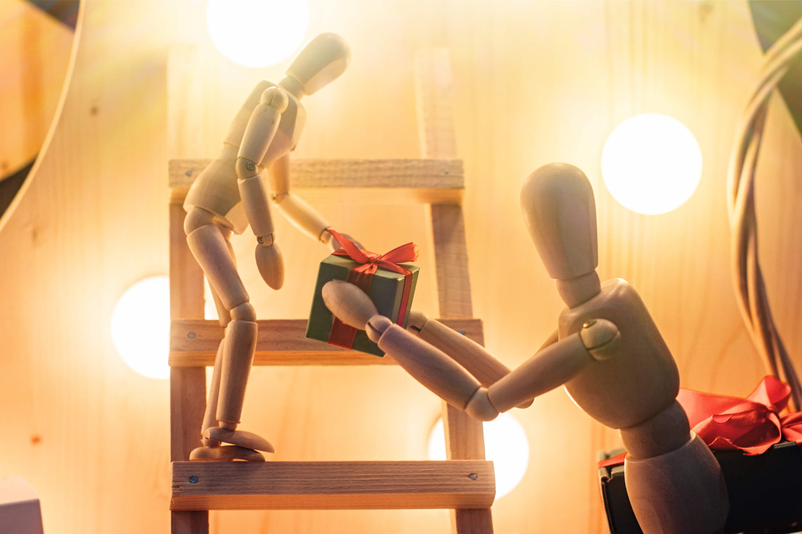 Zwei Holzfiguren übergeben sich ein Geschenk mit einer roten Schleife