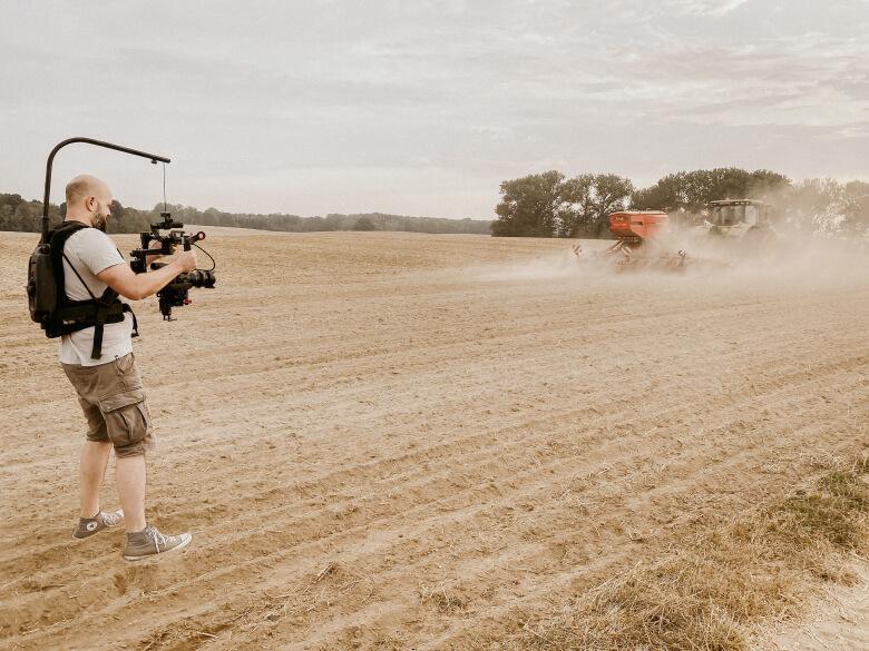 Kameramann am Feld bei einer Produktion für Schulungsvideos