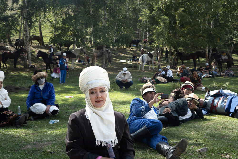 A Kyrgyz woman from the southern part of the country (center) and other onlookers watch the Nomad Game events. Photo by Nic Tanner for NPR