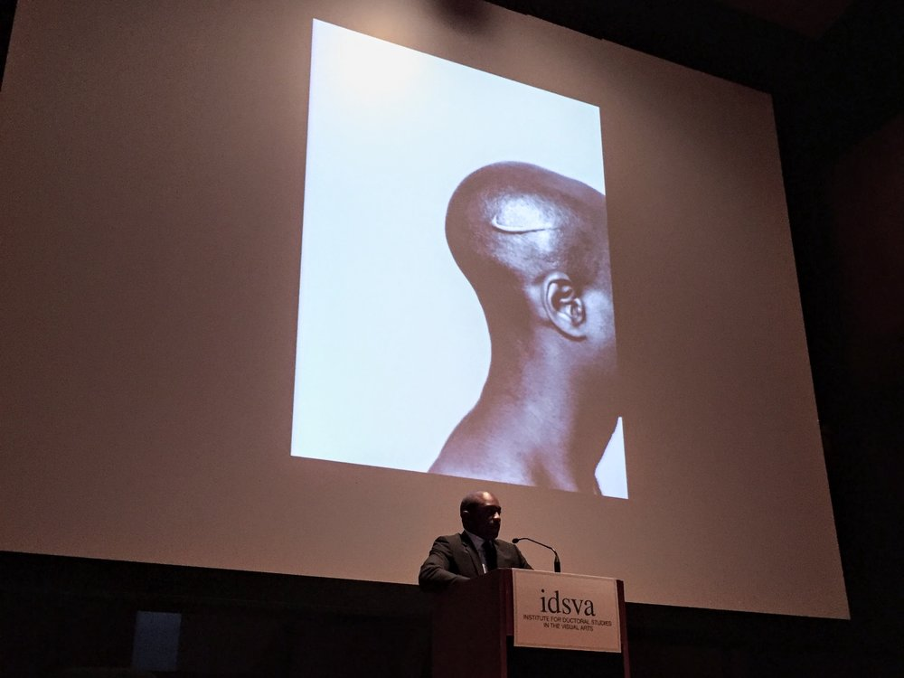 Hank Willis Thomas speaking at the 2017 IDSVA Commencement in NYC with his work Branded Head (2003) displayed. Photo by Simonetta Moro