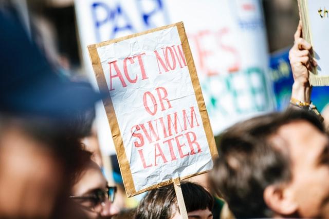"""Affiche d'une manifestation où il est marqué en rouge """"Act now or swin later"""""""