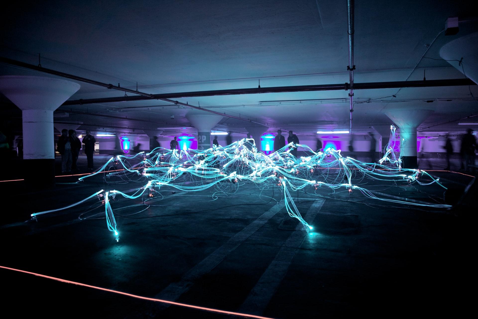 Flot de lumières néon dans une salle d'exposition plongée dans le noir