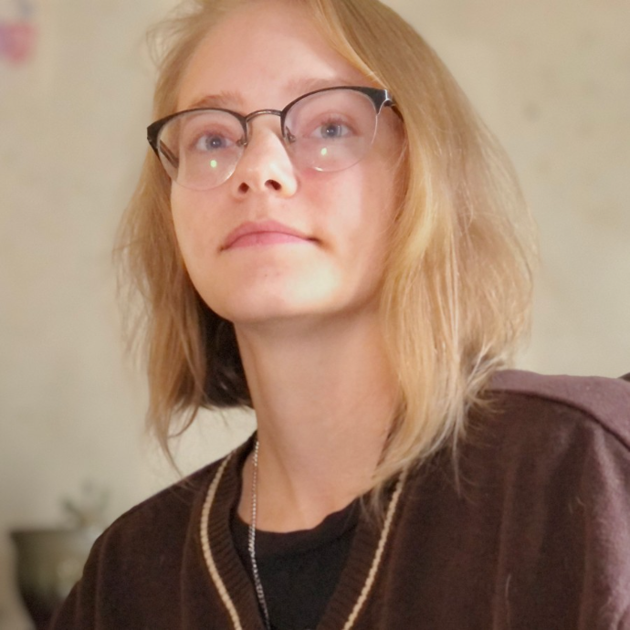 Person with pale skin and blonde hair above shoulder length. They are wearing a brown sweater and glasses