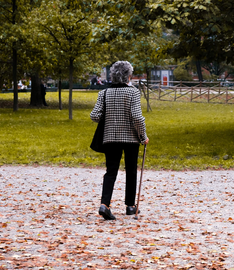 Older woman facing away from the camera walking in a park