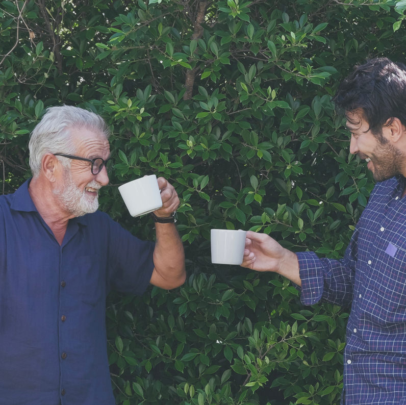 Two men in front of some foliage holding cups looking at each other smiling