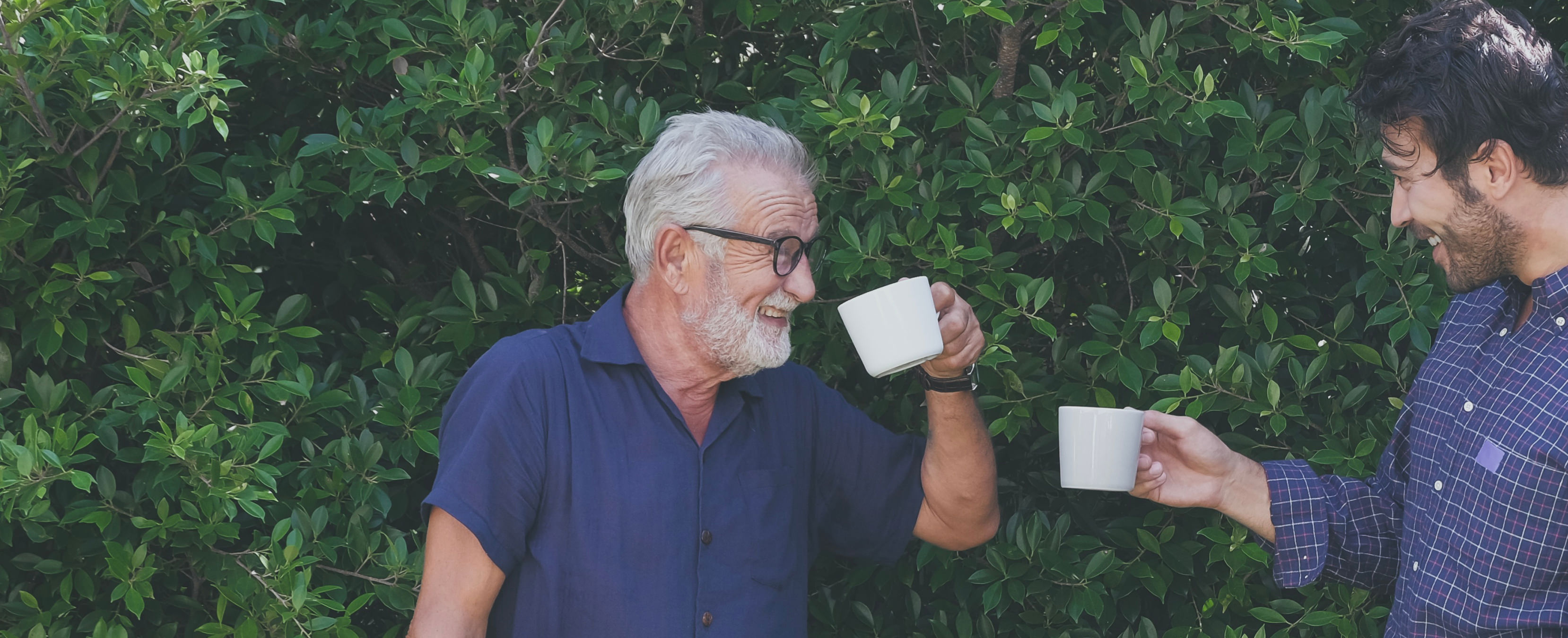 One man in front of some foliage holding up a cup smiling
