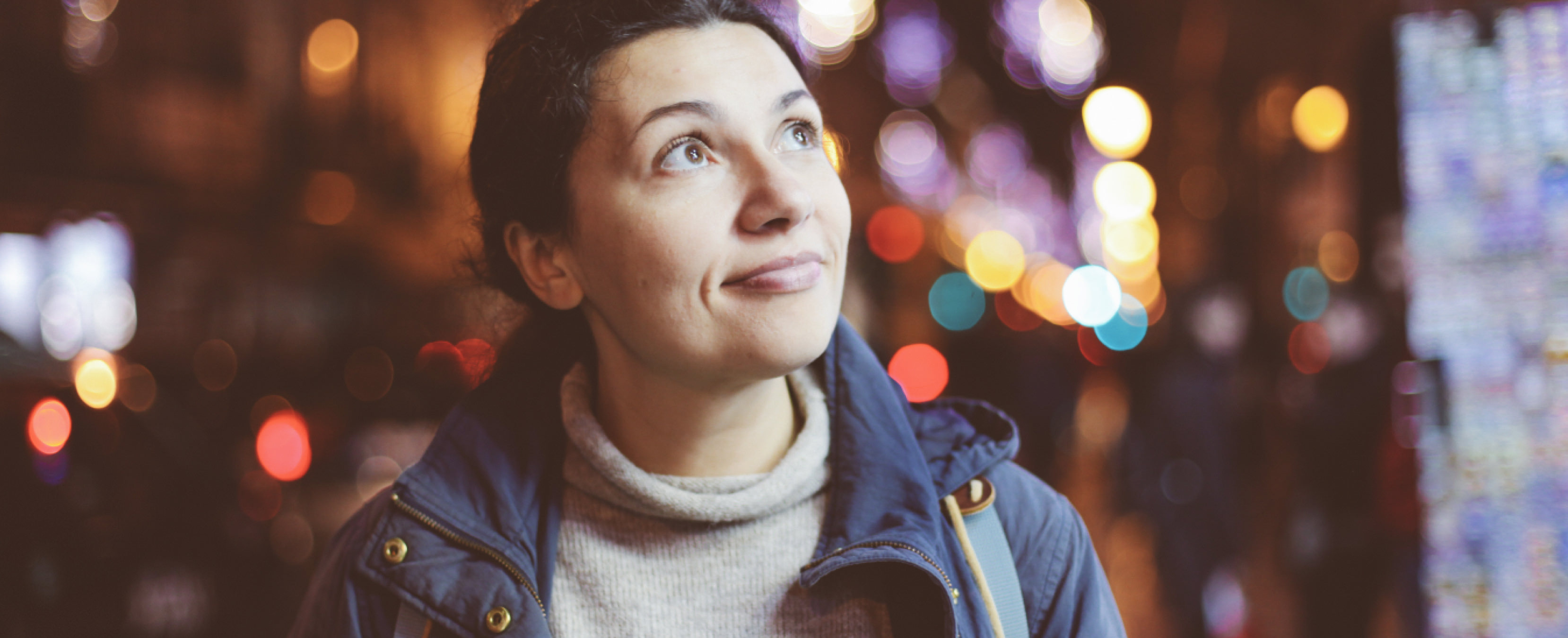 Woman in a city scene with lights in the background looking up smiling