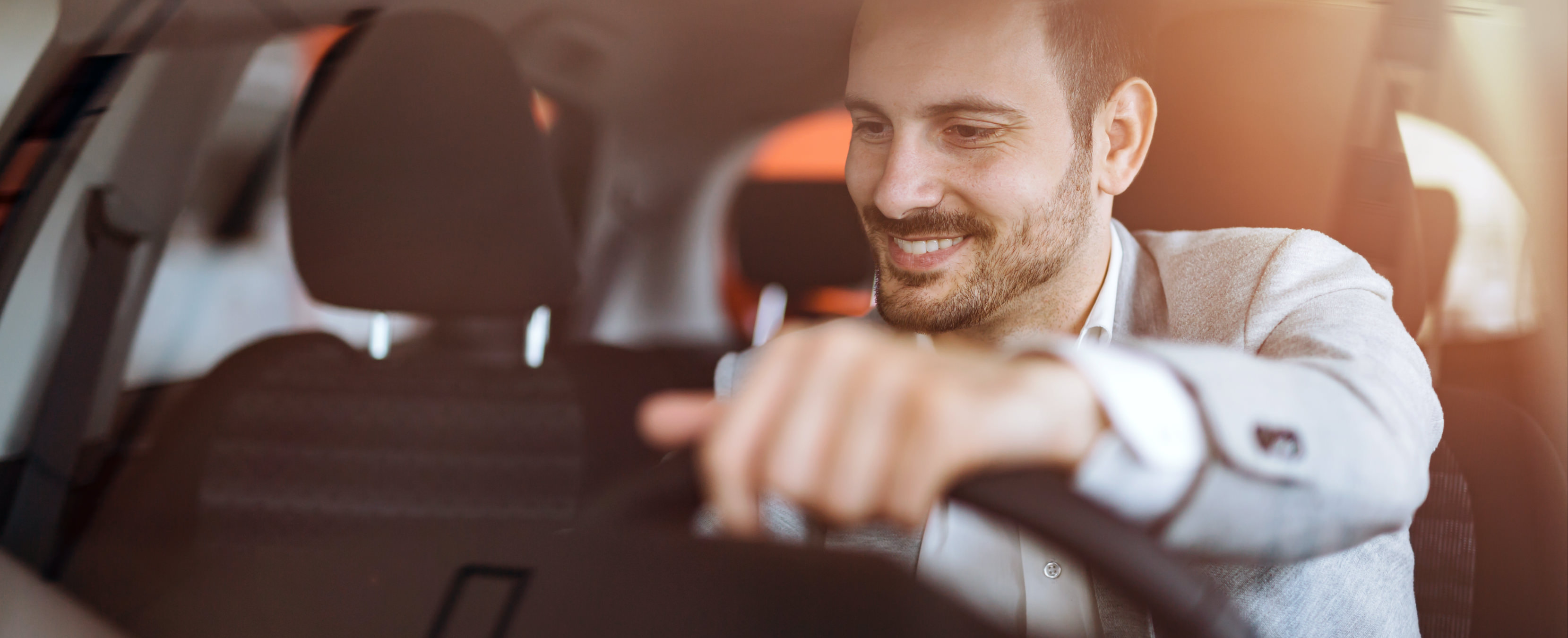 Man in a car smiling engaging with something on the dashboard